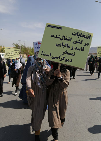 A placard in a protest by the Solidarity Party of Afghanistan's held to condemn the dark days of 28th and 27th April reads 'Elections in an occupied, corrupt, and mafia country is the mockery of democracy!'.